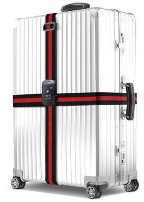 une sangle de valise rouge et noir de la marque BEZ installee sur une valise rigide grise